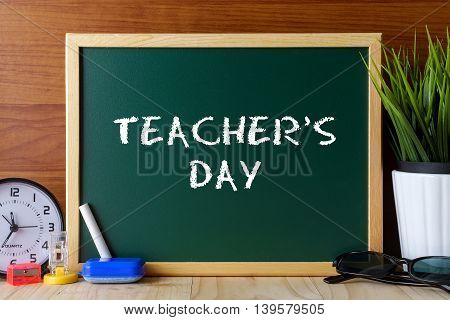 Words Teacher's Day Written On Green Chalk Board On Wooden Table.