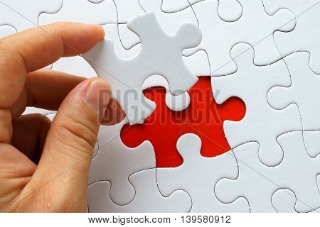 Hand holding a piece of white puzzle