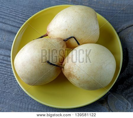 Yellow Pears On The Plate On A Rustic Table