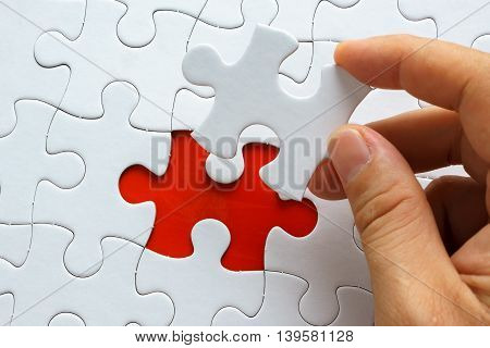 Hand holding piece of blank jigsaw puzzle.