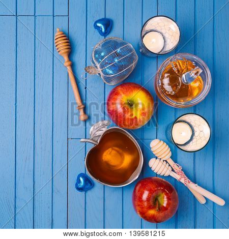 Jewish holiday Rosh Hashana still life with honey apples and candles on wooden blue table. View from above. Flat lay