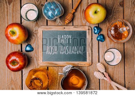 Jewish holiday Rosh Hashana background with chalkboard honey jar and apple on wooden table. View from above. Flat lay