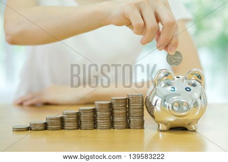 saving money-young woman putting a coin into a money-box-close up