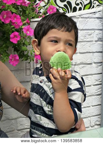 Toddler boy eating an ice cream green in a cream cone, a woman's hand hugging boy