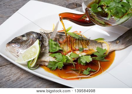 Grilled fish with soy sauce served on a white plate