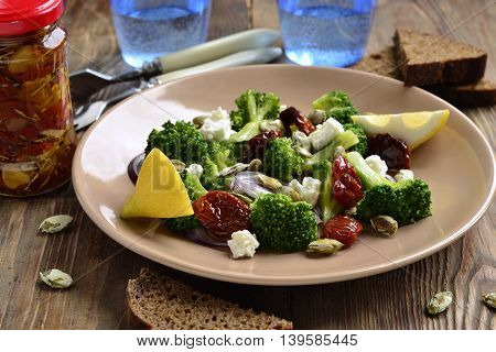 Salad with broccoli dried tomatoes feta onions and pumpkin seeds