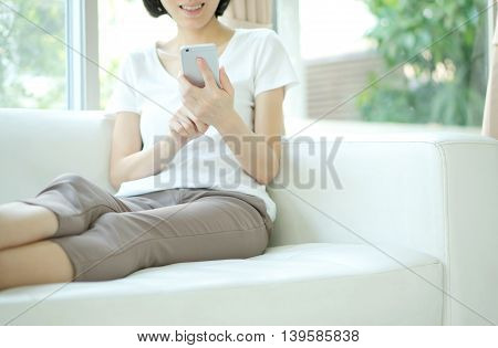 Young Woman Using Mobile Phone On Sofa At Home