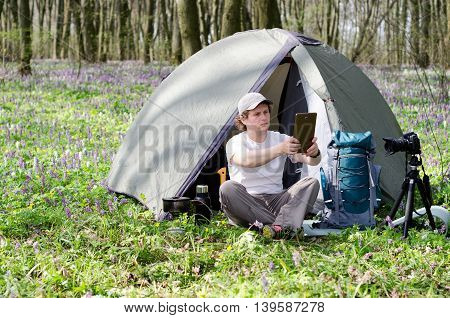 Backpacker photographer uses a tablet outdoors.  Camp ground.