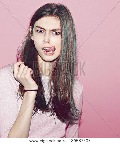 Emotional pretty young hipster girl make funny face on background .