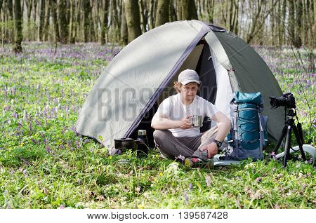 Tourist drinks tea in a tent camp. Beautiful spring forest with a lot of spring flowers.