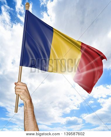 Person's hand holding the Romanian national flag and waving it in the sky, 3D rendering