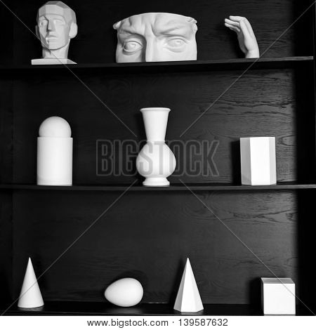 Simple abstract  sculpture. White plaster geometric figures and parts of bodies for art and decorations on a black tree. Mysterious and unusual design of the walls in the interior. View of the form.