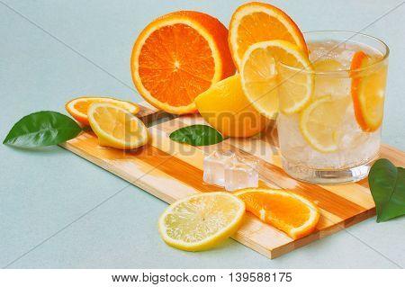 orange lemon leaves glass homemade lemonade and ice on wooden board on gray cardboard surface