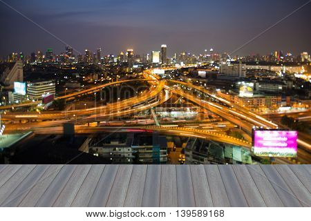 Opening wooden floor, Abstract blurred bokeh light city business background and interchanged road night view