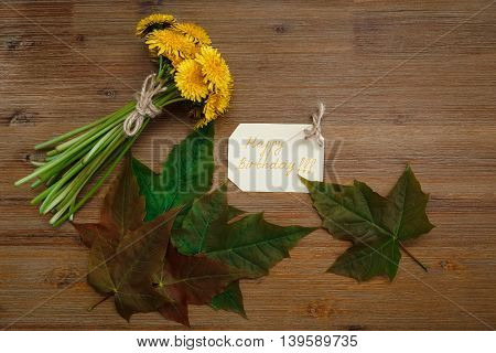 Bunch of Yellow Dandelions,Birthday Wish Card,Green Leaves.Autumn Garden's Background.Wooden Table.Top View