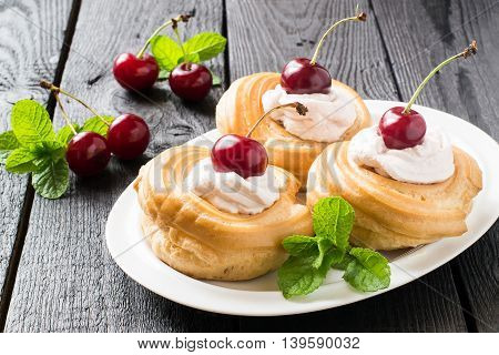 Delicious cakes of choux pastry with cream and cherries. Ripe cherries and mint on a dark wooden table