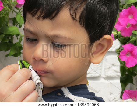 Portrait of a boy, whose mother's hand wipes his mouth with a handkerchief