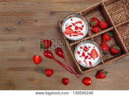 Two Glasses of Yogurt,Red Fresh Strawberries in the Rattan Box with Plastic Spoons on the Wooden Table.Breakfast Organic Healthy Tasty Food.Cooking Vitamins Ingredients.Summer Fruits.Top View