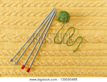 Yellow Knitted Background with Pattern and Braids;Grey Knitting Needle and Green Ball.Hand Made;Fancywork.