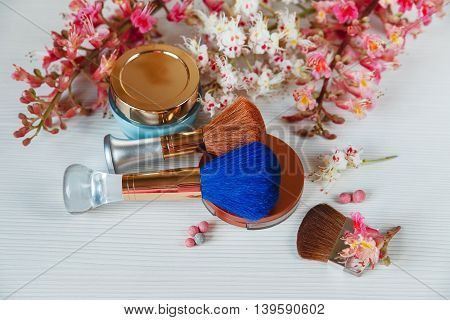There White and Pink Branches of Chestnut Tree,Bronze Powder with Mirror and Make Up Brown and Blue Brushes with Cream are on White TableTop View