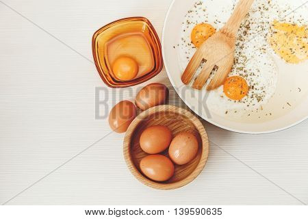 Fried eggs in the frying panbreakfast ingredients,kitchen accessories.Fresh Brown Eggs in the Wooden Plate.White Background.Top View