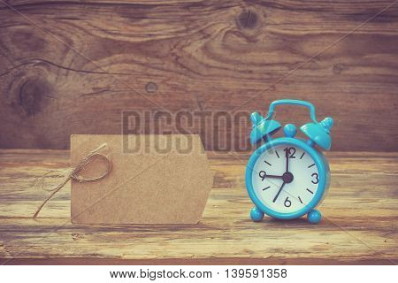 Blue retro alarm clock paper tag with rope on wooden table