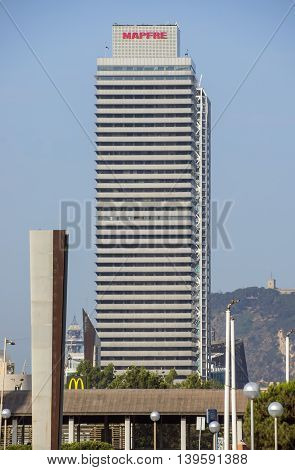 BARCELONA SPAIN - JULY 2 2016: Skyscraper Torre Mapfre in the Olympic Port. It is named after its owner Mapfre an insurance company.