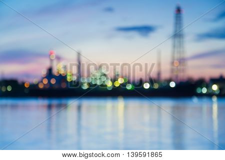 Abstract blurred bokeh lights, heavy industrial refinery riverfront with sunrise sky background