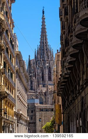 The Cathedral of Barcelona steeple as seen through a narrow alleyway.