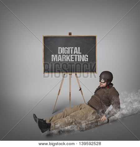 Digital marketing text on blackboard with businessman sliding with a sledge