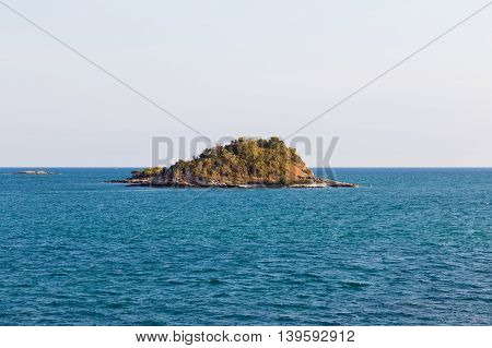 Small lonely island over seacoast skyline, natural landscape background