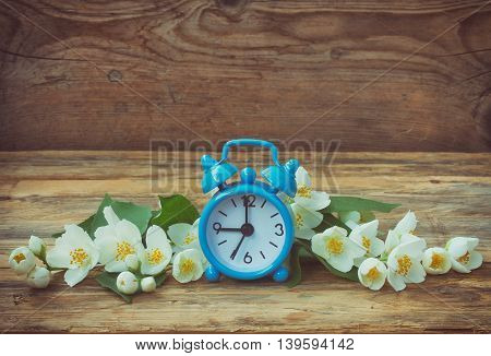 Blue alarm clock jasmine branches wooden surface retro rustic style