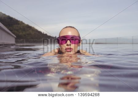 Face closeup of sexy young woman wearing purple sunglasses looking at camera in infinity rooftop swimming pool on a sunny day over blue sky and green trees landscape