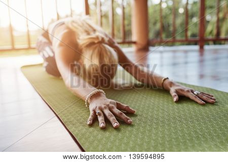 Woman stretching forward performing a yoga pose on exercise mat. Fitness female performing balasana yoga at gym focus on hands.