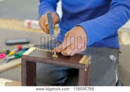 A carpenter hammering Nail heads on to a Traditional Chest made of wood, locally called as Sanadeeg Mubayata, which is used for storing clothing and personal items in Bahrain