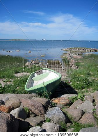 Lonely boat on the beach amond the stones.Fishing boat.