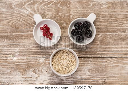 Top view of blackberries redcurrants and oats in ceramic bowls on whitewashed wood surface