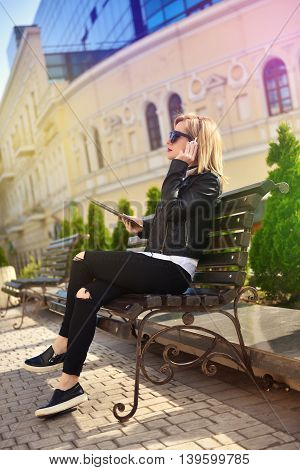 hipster girl with tablet sitting on bench and listening music