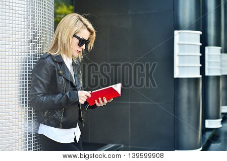 young hipster girl reading red book close up