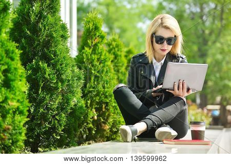 hipster girl sitting with a laptop and working