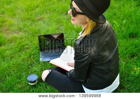 happy hipster girl sitting with laptop in hand view from above