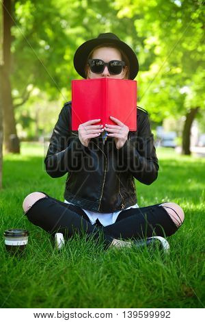 hipster girl in hat sitting on grass with book