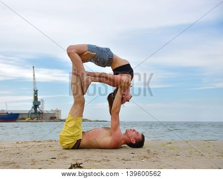 woman and man doing acrobatic yoga on a beach
