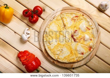 Pizza on light wooden background top view. Thin pastry crust on wooden desk