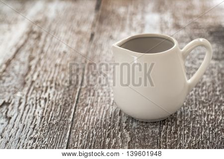 White Gravy Boat On A Rustic Wooden Background