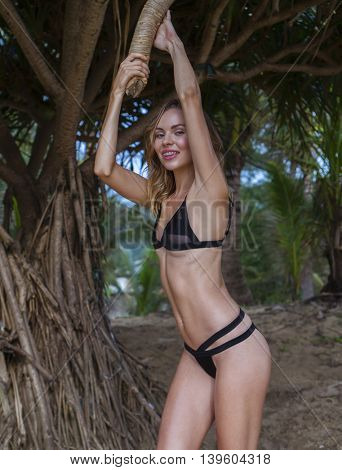 Beautiful blonde glamour woman wearing black swimwear posing on a beautiful summer day between palm trees