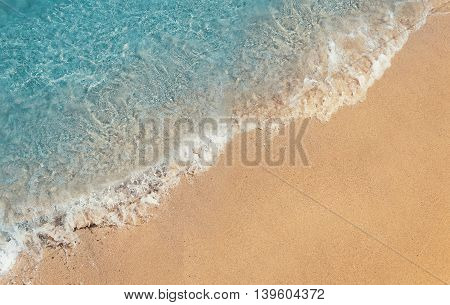 Soft foaming wave of blue sea on a sand beach. Summer vacation background holiday recreation concept
