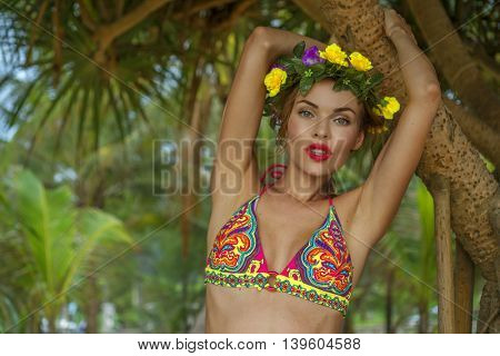 Closeup of beautiful blonde glamour woman wearing colourful swimwear and wreath posing on a beautiful summer day between palm trees