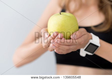 Source of health. Close up of green apple in hands of pleasant sporty woman holding it while going to eat
