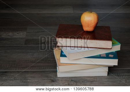 pile of books with an apple on top on the wooden background